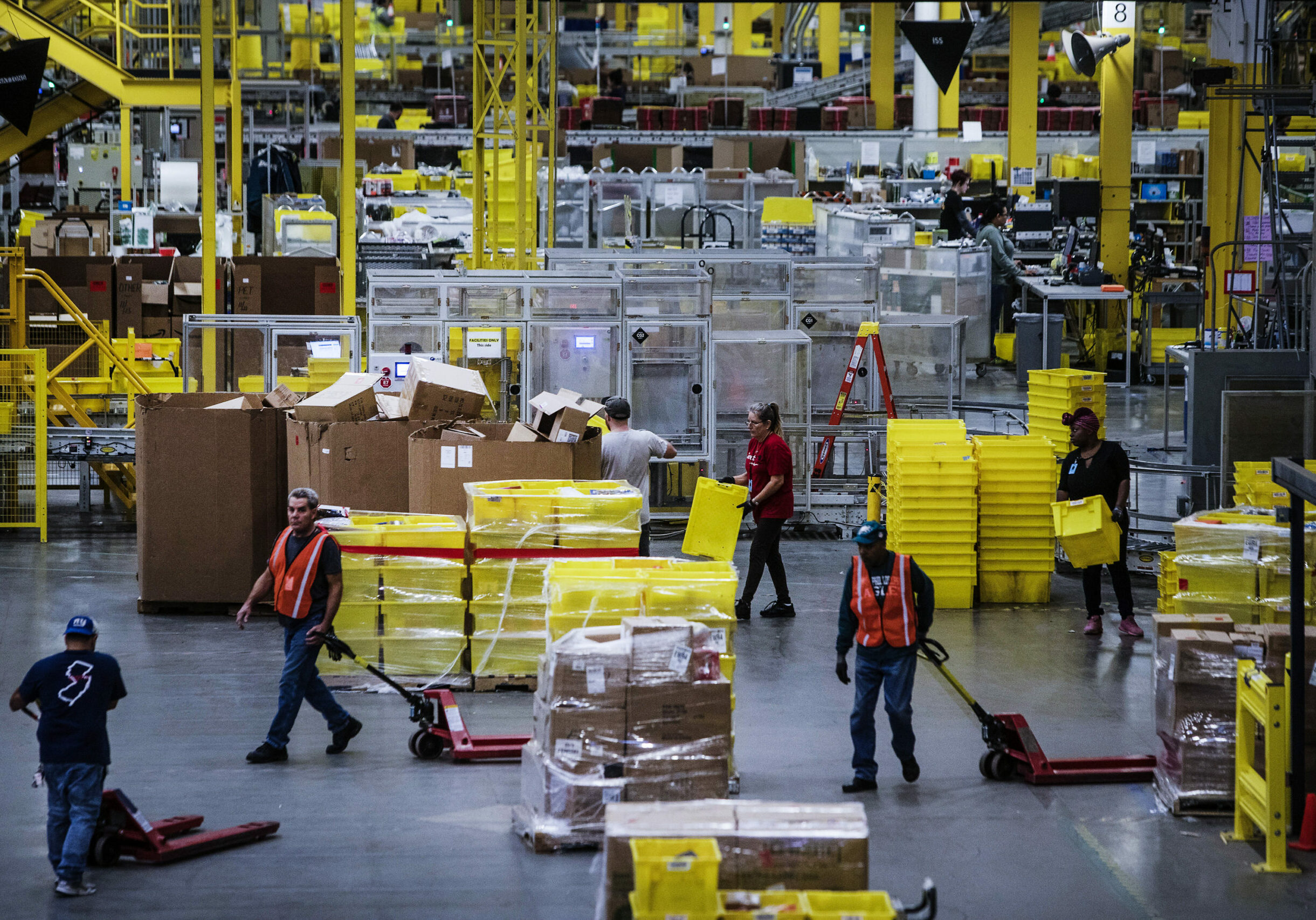Employees pull pallet trucks at the Amazon.com Inc. fulfillment center in Robbinsville, New Jersey, U.S., on Monday, Nov. 27, 2017. The holiday shopping season is off to a strong start and retailers appear to be continuing the momentum today --CyberMonday-- the biggest online spending day of the year. Photographer: Victor J. Blue/Bloomberg via Getty Images