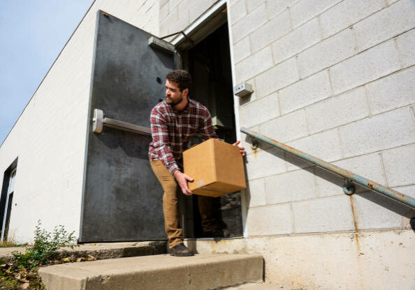 Loos Prevention topic.  A male warehouse employee placing a box outside a back door of an industrial warehouse distribution building.  A typical internal employee theft scenario.